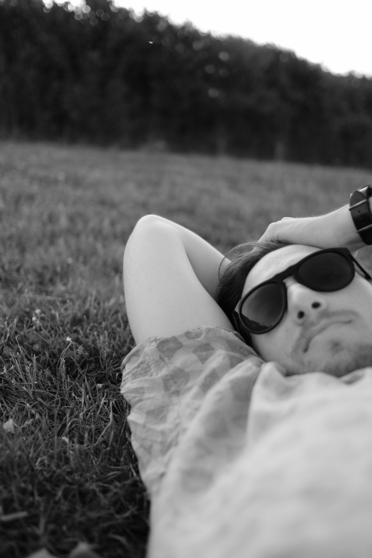 A man in sunglasses lays in the grass, holding his arm behind his head looking towards the camera.