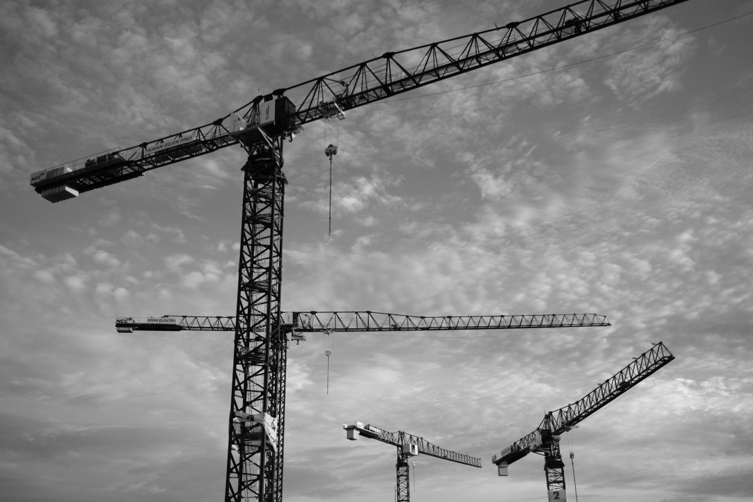 Image of four cranes set on a black and white clouded background
