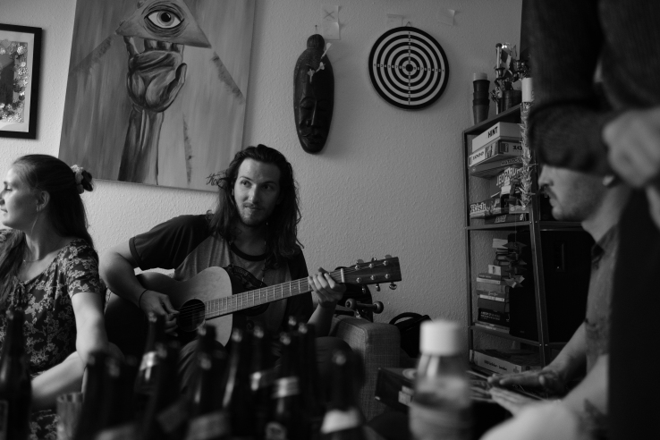 A man holds a guitar in a living room among many partygoers and a table full of empty beer bottles.