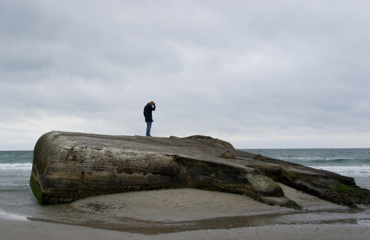 A man stands on a concrete bunker on the side of a beach...